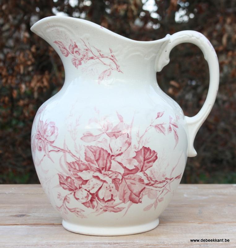 Antieke waterkan met roze bloemen